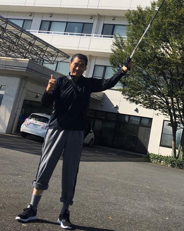 病院前で明るい笑顔を見せる谷津
