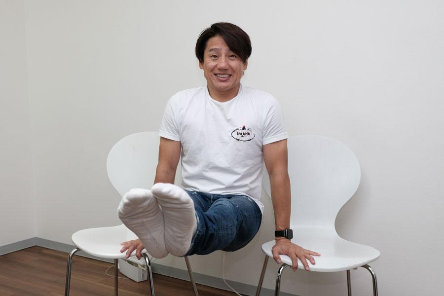 """【写真】体脂肪率13~14%で""""脚前挙""""の姿勢も笑顔で余裕【写真:山田隆】"""