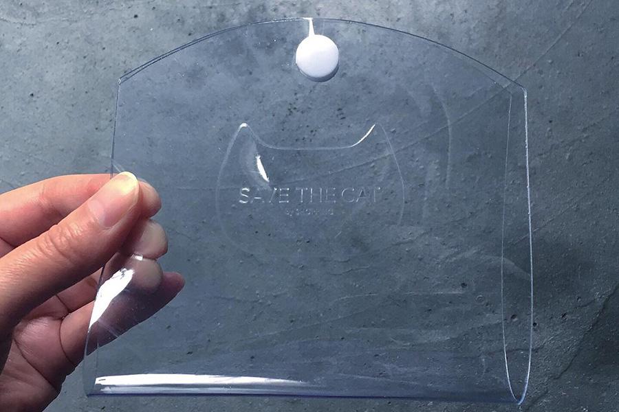 塩ビ素材で、ボタンの色はホワイトの他にブラックも。バッグの表には猫の形と「SAVE THE CAT」のメッセージが刻印されている。