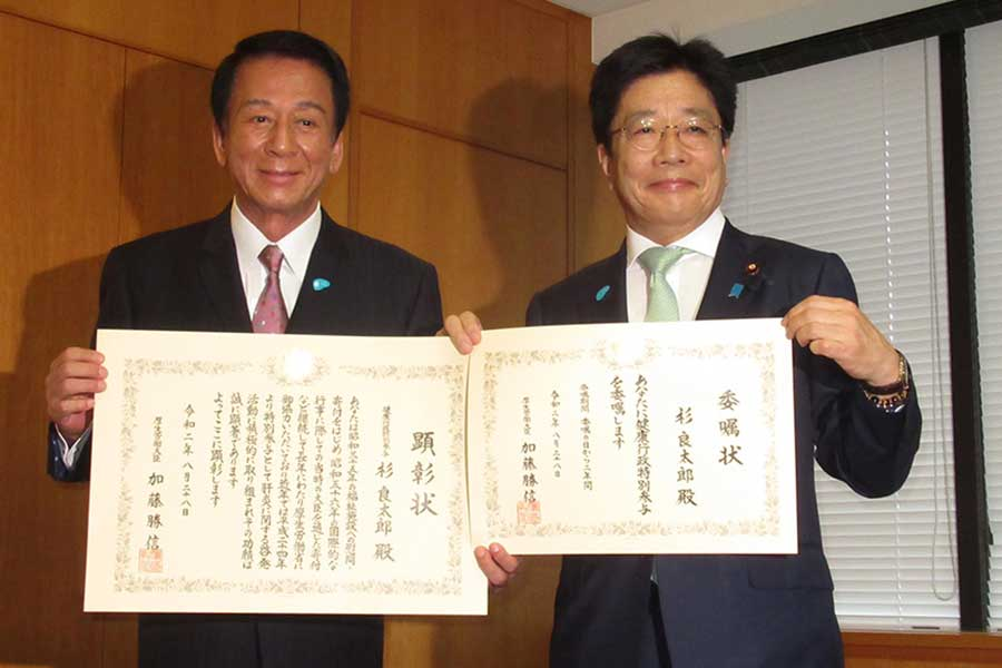 加藤勝信厚生労働大臣(右)から「厚生労働大臣顕彰状」と「健康行政特別参与」の委任状を手渡された杉良太郎【写真:ENCOUNT編集部】