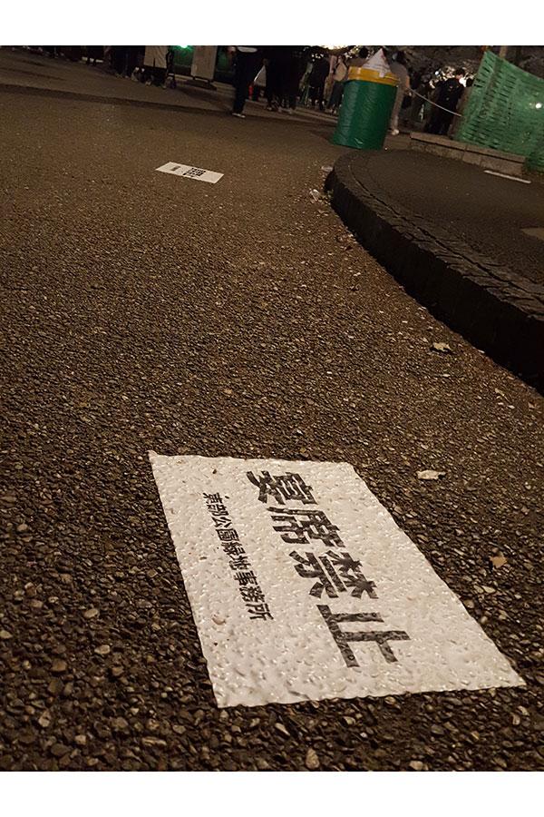 地面に貼られた「宴席禁止」の注意書き。しかし、あちこちで宴会がスタート 【写真:ENCOUNT編集部】