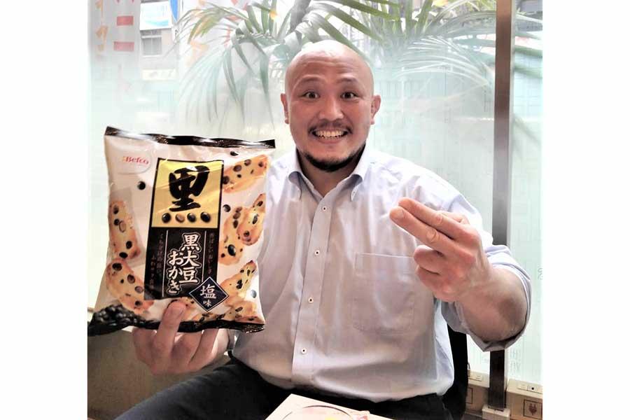岡林裕二は大好きな塩味の黒豆おかきを手にピッサリ【撮影:柴田惣一】